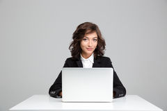 Lächelndes schönes Sitzen und Anwendung der jungen Frau des Laptops lizenzfreie stockfotografie