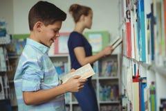 Lächelndes Schülerlesebuch in der Bibliothek Lizenzfreie Stockfotos
