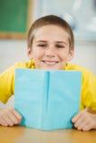 Lächelndes Schülerlesebuch in einem Klassenzimmer Lizenzfreies Stockfoto