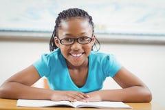 Lächelndes Schülerlesebuch in einem Klassenzimmer Stockfotos