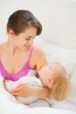 Lächelndes schlafendes Schätzchen der jungen Mutterholding Stockfotos