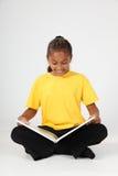 Lächelndes Schulemädchen 10, das einen Buchstift lesend sitzt Lizenzfreies Stockbild