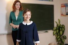 Lächelndes Schulmädchen führt die Aufgabe an der Tafel durch Ausbildung lizenzfreies stockbild