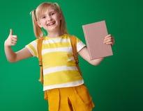 Lächelndes Schulmädchen mit dem Buch, das sich Daumen zeigt Stockbild