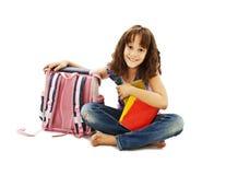 Lächelndes Schulmädchen mit dem Rucksack, der Bücher anhält Lizenzfreie Stockfotografie