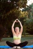 Lächelndes schwangeres übendes Yoga an der Natur lizenzfreies stockfoto