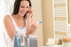Lächelndes Schwangerschaft-Testergebnis der Frau positives lizenzfreie stockfotografie