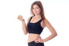 Lächelndes seitlich stehen des schönen Mädchens untersucht den Abstand und das Halten eines Apfels Stockbilder