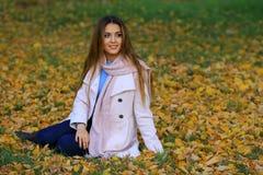 Lächelndes Sitzen der jungen Frau auf dem Gras im autum Ahorn-Gartenhintergrund des Falles gelber Stockfoto