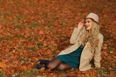 Lächelndes Sitzen der jungen Frau auf dem Gras im Herbst Ahorn-Gartenhintergrund des Falles gelber Schönes Mädchen im Mantel und  Lizenzfreie Stockfotos