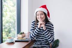 Lächelndes Sitzen des asiatischen Mädchens in der Kaffeestube, Frau, die Santa Cl trägt stockbild