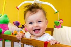 Lächelndes Sitzen des Babys des kleinen Mädchens in ihrem Bett Lizenzfreie Stockbilder
