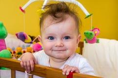 Lächelndes Sitzen des Babys des kleinen Mädchens in ihrem Bett Lizenzfreie Stockfotos