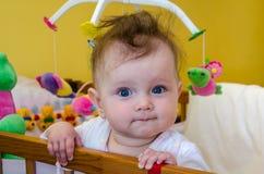 Lächelndes Sitzen des Babys des kleinen Mädchens in ihrem Bett Stockfotos