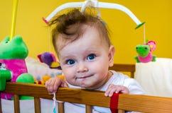 Lächelndes Sitzen des Babys des kleinen Mädchens in ihrem Bett Lizenzfreies Stockbild