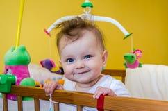 Lächelndes Sitzen des Babys des kleinen Mädchens in ihrem Bett Stockbild