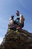 Lächelndes Sitzen des Kerls auf einem Felsen Lizenzfreies Stockbild