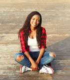 Lächelndes sitzendes Stillstehen der afrikanischen Frau der Junge in der Stadt Stockbild