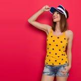 Lächelndes Sommer-Mädchen im gelben Hemd und in der blauen Kappe Lizenzfreie Stockfotografie