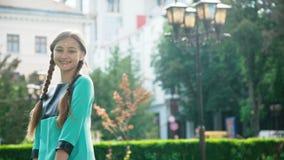 Lächelndes sorgloses Mädchen mit zwei Zopfwegen und Aufstellung am sonnigen Park stock video