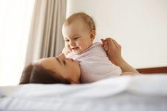 Lächelndes Spielen der glücklichen netten jungen Mutter mit ihrer kleinen Babytochter, die zu Hause im Bett liegt Stockfotografie