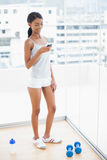 Lächelndes sportliches Modell, das einen Text von ihrem Smartphone sendet Stockfotos