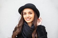 Lächelndes städtisches Mädchen mit Lächeln auf ihrem Gesicht Porträt des modernen gir eine Felsenschwarzart draußen tragend, die  Stockbild
