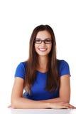 Lächelndes Studentenmädchen, das am Schreibtisch sitzt Lizenzfreie Stockfotografie