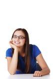 Lächelndes Studentenmädchen, das am Schreibtisch sitzt Stockbild