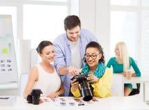 Lächelndes Team mit dem photocamera, das im Büro arbeitet Stockfotografie