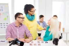 Lächelndes Team mit den Druckfotos, die im Büro arbeiten Stockfotos