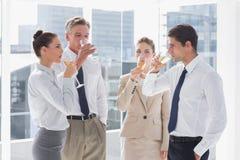 Lächelndes Team von den Geschäftsleuten, die Champagner trinken Stockfotografie