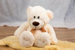 Lächelndes Teddybärspielzeug, das aus den Grund sitzt lizenzfreie stockfotos