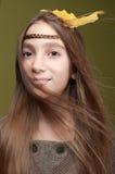 Lächelndes tragendes Gelb des Mädchens verlässt in ihrem Haar lizenzfreies stockfoto