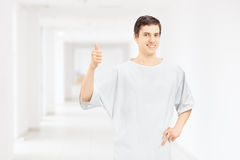 Lächelndes tragendes Krankenhaus des Patienten bekleiden und Daumen aufgebend Stockfotografie