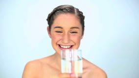 Lächelndes Trinkwasser der jungen Frau stock footage