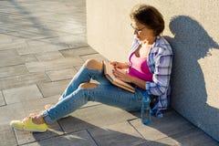 Lächelndes Trinkwasser und Ablesen der Frau eines Buches Städtischer Hintergrund Lizenzfreie Stockfotos