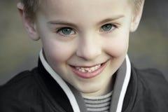 Lächelndes unschuldiges Kind mit vollkommenen blauen Augen Stockbilder