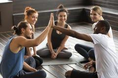 Lächelndes verschiedenes Yogateammitgliedgeben hoch--fünf an Gruppe trai stockbilder