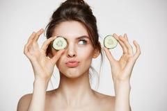 Lächelndes versteckendes Auge des jungen schönen nackten Mädchens hinter Gurkenscheibe über weißem Hintergrund Schönheit Badekuro stockfoto