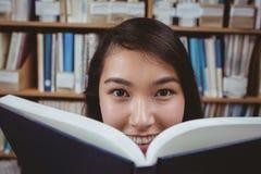 Lächelndes versteckendes Gesicht des Studenten hinter einem Buch Stockfotografie