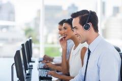 Lächelndes Vertreter, das in einem Call-Center arbeitet Lizenzfreie Stockfotos