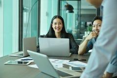 Lächelndes verwendendes und mit ihren Kollegen sprechend Geschäftsmädchen lizenzfreie stockfotografie