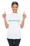 Lächelndes vorbildliches tragendes freiwilliges T-Shirt, das Daumen aufgibt Lizenzfreies Stockfoto