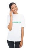 Lächelndes vorbildliches tragendes freiwilliges T-Shirt, das einen Telefonanruf hat Stockbilder