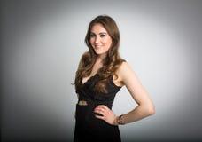 Lächelndes weißes Brunettemodell im schwarzen Kleid lizenzfreie stockfotografie