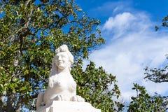 Lächelndes weibliches Gesicht im Sphinxkörper im mittelalterlichen Garten Lizenzfreies Stockbild