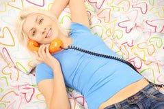 Lächelndes weibliches Lügen im Bett und Unterhaltung an einem Telefon Lizenzfreie Stockbilder