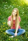 Lächelndes weibliches Sitzen auf dem Feld des Löwenzahns Stockfotos