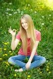Lächelndes weibliches Sitzen auf dem Feld des Löwenzahns Lizenzfreie Stockfotografie